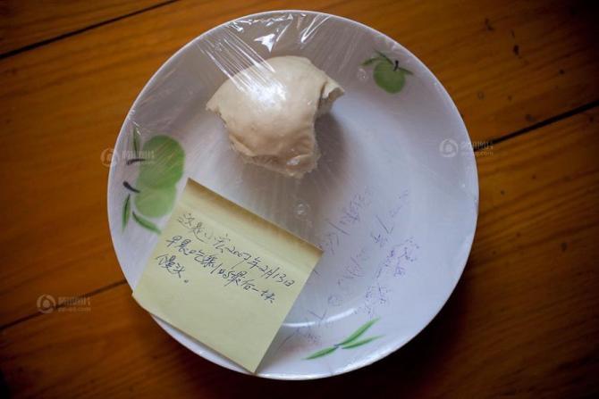 """失独父亲——潘教授保存这块馒头已经5年了,贴着一张小纸条写着:""""这是小宏2007年2月13日早晨吃剩下的最后一块馒头。"""""""