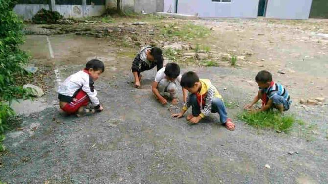 学校的操场坑洼不平、乱石嶙峋,180名大小学童只能在砂石堆里呼吸阳光,学校唯一的活动场所里,泥土和石子是孩子们最好的伙伴。因为乒乓球台周围全是凹凸不平的石块,水泥球台成了孤独的摆设。